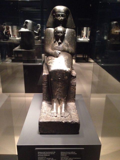 Estatua del funcionario de la corte Senenmut con la princesa NeferureDios en exposición en Caixa Forum