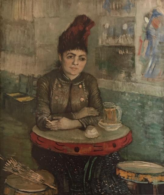 """En el café Agostina Segatori en """"Le Tambourin"""". Óleo sobre lienzo En este cuadro centra la vista del espectador en Agostina inclinada sobre la mesa característica que da nombre al local (pandereta). También, desvía la imagen del espectador hacia el fondo del cuadro remarcando unas sillas con tonos amarillos para contemplar el resto de la escena que pinta y donde puede verse alguno de los grabados japoneses que expuso en el café."""